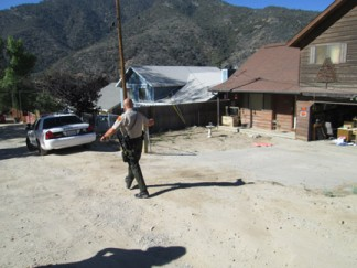 A sheriff's deputy goes to nearby homes to speak with residents about a potential danger. [photo by Gary Meyer]