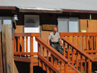 A sheriff's deputy goes door to door at homes adjacent to the scene where the possible explosive was found. [photo by Gary Meyer]