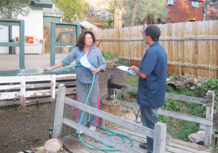 Otilia Herrera was watering her plants when Rafael Molina, Jr. handed her an emergency water conservation notice on Tuesday evening. Molina went door to door alerting the community on behalf of the water company.
