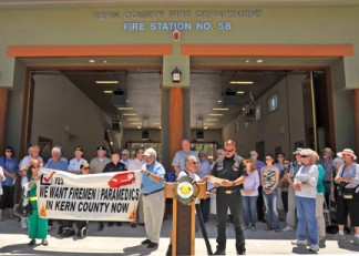 About 200 people came to the ribbon cutting and pre-opening ceremony at Kern County Fire Station 58 near Pine Mountain Village July 12. Above, Frances Durocher and William Gurtner hold the banner which is now a historic symbol of the remote community's struggle to gain better emergency medical response. At the podium, A.J. Durocher presents Kern County Fire Chief Brian Marshall with historical clippings from The Mountain Enterprise about the last decade of the effort. At right, community leader Edie Stafford looks on with pride. [photo by Mel Weinstein]