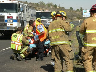 Firefighters worked to extricate Lana Rains from the crushed Taurus which was spun around by the impact of an oncoming truck at the intersection of Mt. Pinos Way and Frazier Mountain Park Road. [photo by The Mountain Enterprise]