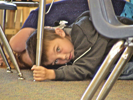 Kindergarten student at Frazier Park School practicing earthquake preparedness drill last week. [photo by Patric Hedlund]