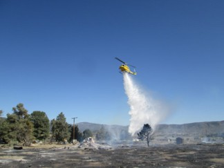 A Ventura County Sheriff's helicopter drops water on a debris pile thought to be the origin of the fire. [photo by Gary Meyer]