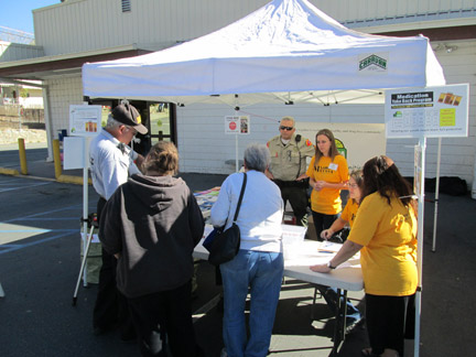 (l-r) Sheriff's Volunteers Mike Hall and Carol Trudeau, Kern County Sheriff's Sergeant Mark Brown, and MCCASA volunteers Tina Fessia, Marie Marot and Lisa Walter assist local residents to turn in their medications for disposal. [photo by Gary Meyer]