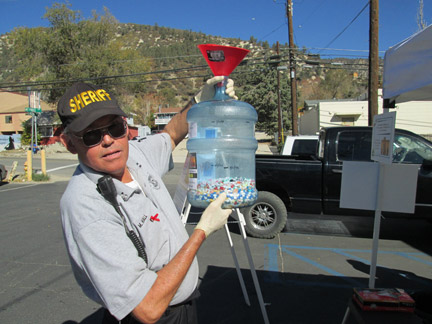 Sheriff's Volunteer Mike Hall shows the bottle of pills collected by 11 a.m. at the Drug Take Back event. [photo by Gary Meyer]