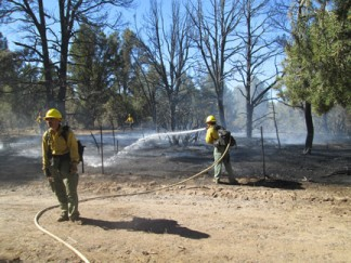 Los Padres National Forest firefighters from the Mt. Pinos Ranger District keep the water flowing at the scene of the fire near Mill Canyon Road. [photo by Gary Meyer]