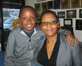 Nide Zimemo (right) with her son Nehemiah, 7 (sitting on a counter next to Mom). Zimemo has lived in the U.S. for 13 years, but was born and raised in South Africa. She is reflecting on Nelson Mandela's impact on her life. [photo by Gary Meyer]