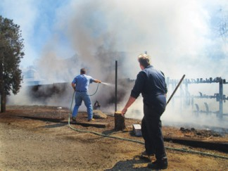Piñon Pines resident Steve Newman (left) uses a garden hose to keep flames from moving north along a wood fence to a stand of trees between two homes. Joe Fuess (right) runs to tear apart the fence to remove fuel from the fire's path toward the homes. [photo by Gary Meyer]