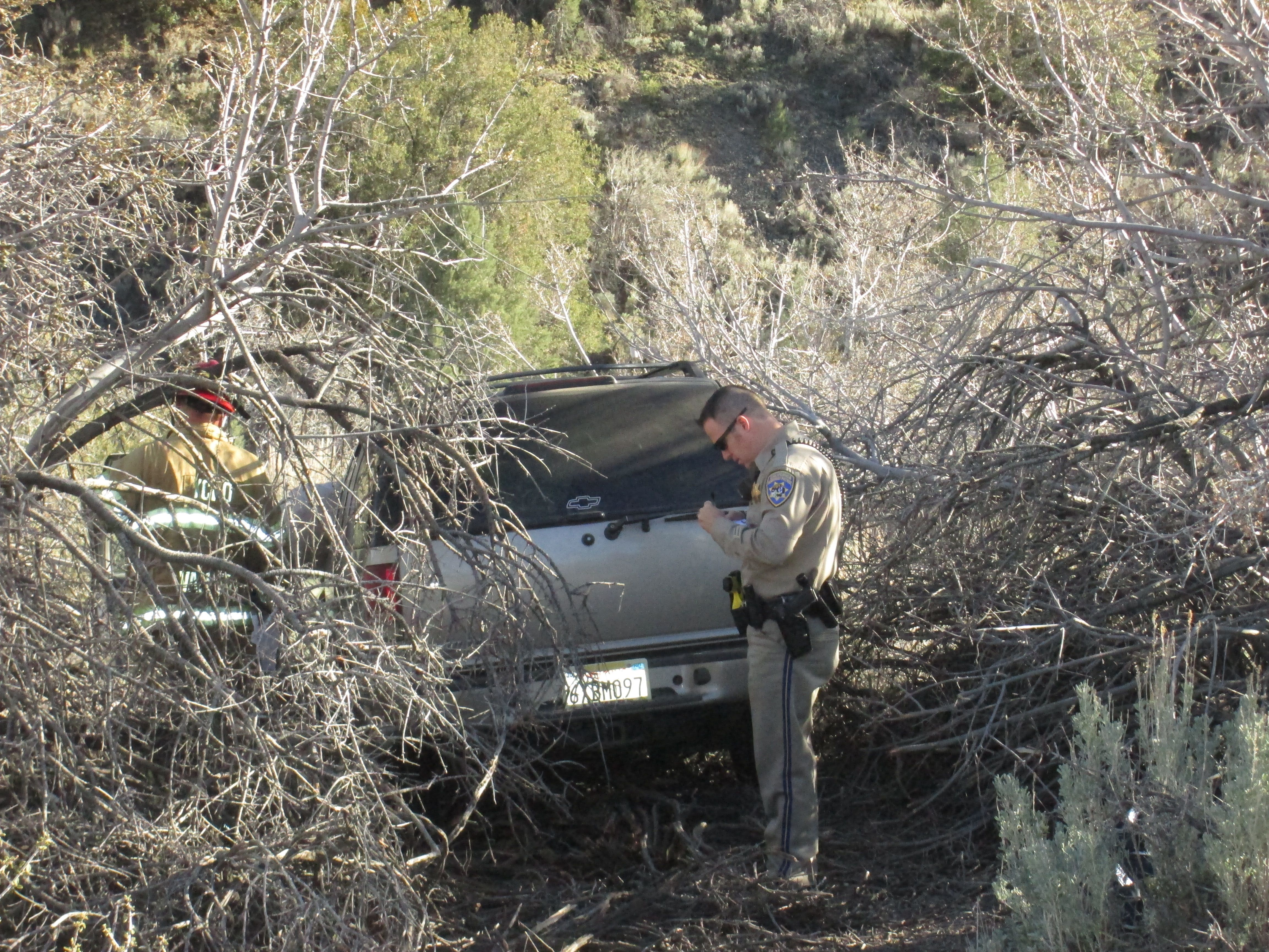 The silver Chevy SUV came to rest in vegetation on the creek side of the hill. It did not appear to have rolled over. The driver was extracted from the car and put on a stretcher. [Gary Meyer photo]