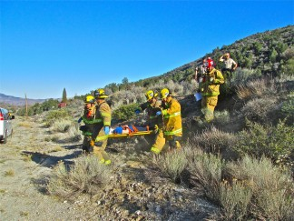 The driver of the silver Chevy SUV that went off Frazier Mountain Park Road Wednesday, over the hill shown here and down the other side, is carried on a stretcher to the ambulance.