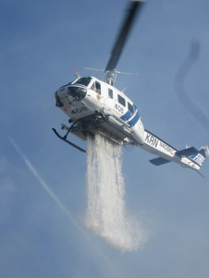 Kern County Helicopter 408 drops water from the Tait Ranch pond. [photo by Gary Meyer]