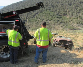 Santana Molina and a driver from Mountain Towing haul the Toyota Corolla up from the 100-foot embankment. [photo by Gary Meyer, The Mountain Enterprise]