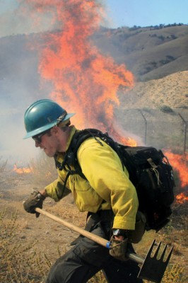 A crew member of Kern County Fire Department helicopter 408 battling against a wall of fire in Lebec on Sunday, July 7. [photo by Jeff Zimmerman]