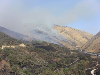 A grass fire (named the Water fire) rushes up hills toward Digier Canyon, driven by winds. [photo by The Mountain Enterprise]