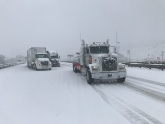 Big rigs (yep, including Fed Ex) are stuck in the snow on the Grapevine, which has been closed in both directions [Jeff Zimmerman photo, near Gorman, Dec. 6, 10:40 a.m. ]