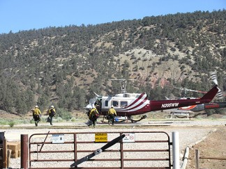 Flight crew members board a helicopter at Chuchupate Ranger Station for the short trip to the fire where they will begin setting up air operations. [photo by Gary Meyer, The Mountain Enterprise]