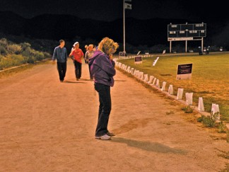 Kay Chilano reads the inscriptions on luminaria around the track. [photo by Patric Hedlund]