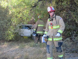 Firefighters used a chain saw to remove willow branches surrounding a white Kia that left Mil Potrero Highway and hit a tree at about 9:10 a.m. Thursday morning. A woman was killed. [Patric Hedlund photo]