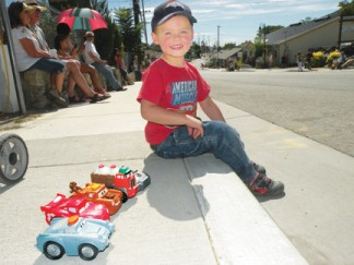 James Crippen, 3 ready and waiting in 2013 for the Fiesta Days Parade to start down Mt. Pinos Way, toys all lined up in a row. [photo by Patric Hedlund]