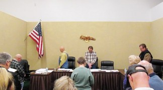 After reading a prepared statement, Lebec County Water District Board President Michael Hightower leads the public meeting in a minute of silent prayer and meditation. [photo by Gary Meyer]