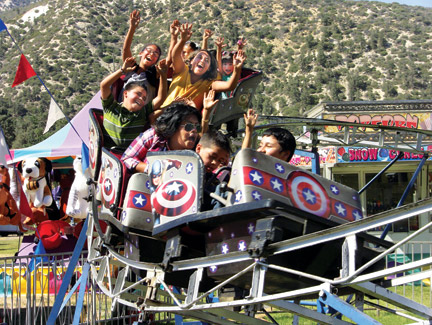 Fiesta Days-goers scream along the roller coaster in earlier years of the festival. [photo by Gary Meyer]