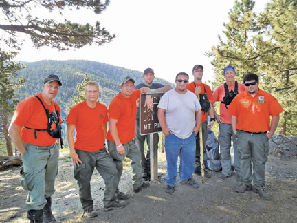 "These members of the Southern Kern Search and Rescue unit took a rigorous night training hike on June 29, 2013. They are (l-r) Steve Packard, David Atwell, Michael DeLeo, Cody Salyards, Scott Parker, Taylor Dubois, Doug Wilde and Mike Parker, Jr. Unit Captain Frank Heilman took the photo. This photo was taken at 8 a.m. at the Cerro Noroeste Peak trail head after completing an all-night training hike that left from the Mil Potrero ""Y"" at the base of Mount Pinos (and Mil Potrero Highway) at 7 p.m. June 28. See SKSAR recruitment ad on page 3.[photo by Unit Captain Frank Heilman]"