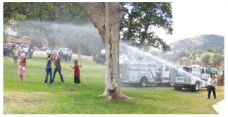 Kids frolic under the spray of a fire department water hose during a Boys & Girls Club event in 2006. [photo by Patric Hedlund]