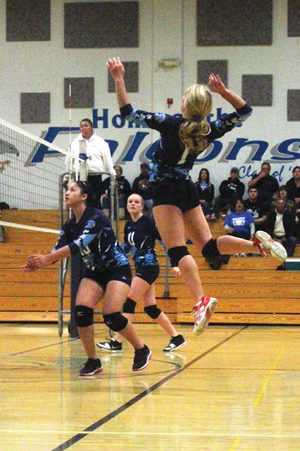Rachel Rivette hangs in the air before slamming the ball down at the Bishop Knights. [photo by Cliff Coleman]