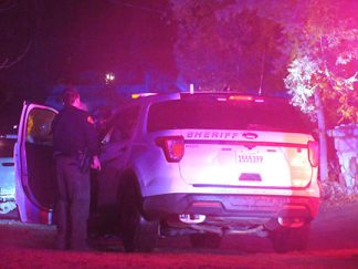 [Kern County Sheriff's deputies take cover behind a vehicle while negotiators speak with an armed man in a Frazier Park house; photo by Gary Meyer, The Mountain Enterprise]